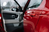 selective focus of shiny car door of red automobile