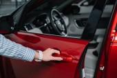 oříznutý pohled mladé ženy otevírající dvířka v červeném automobilu