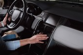 Fotografia cropped view of young woman touching buttons while holding steering wheel in car