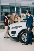 car dealer giving key to cheerful friends standing near white car
