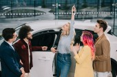 Fotografie car dealer looking at happy blonde girl holding key near friends in car showroom