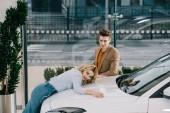 schöner Mann schaut attraktives blondes Mädchen an, das weißes Auto berührt