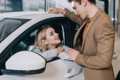 pohledný muž, který se dívá na atraktivní blonďatou dívku sedící v autě