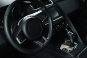 Fotografia selective focus of steering wheel near gear shift handle in luxury car