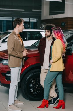 handsome man talking with friends near automobiles in car showroom