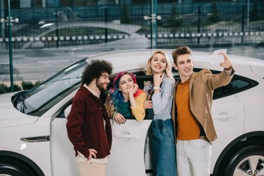cheerful group of friends taking selfie on smartphone near white car