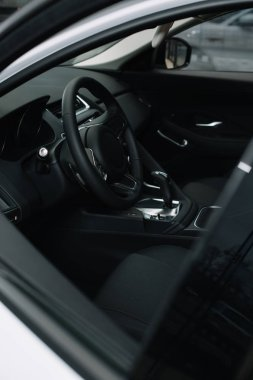selective focus of black steering wheel near gear shift handle in luxury car