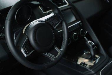 selective focus of steering wheel near gear shift handle in luxury car