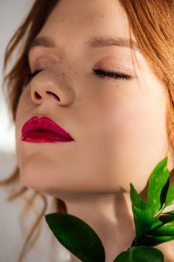 Portrait of beautiful young redhead woman with red lips and eyes closed posing with green leaf stock vector