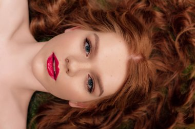 top view of beautiful young redhead woman with red lips looking at camera
