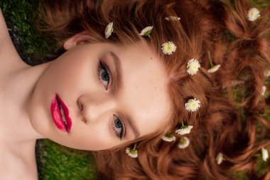 Beautiful young redhead woman with red lips and chrysanthemum flowers in hair looking at camera stock vector