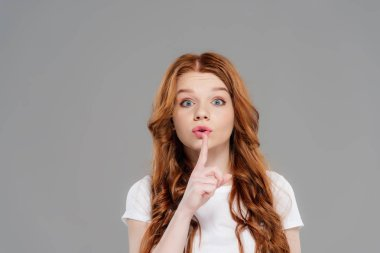beautiful redhead girl looking at camera and doing silent gesture isolated on grey