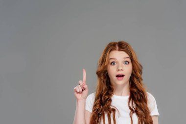 beautiful surprised redhead girl looking at camera and showing idea gesture isolated on grey with copy space