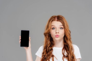 beautiful redhead girl with duck face looking at camera and showing smartphone with blank screen isolated on grey