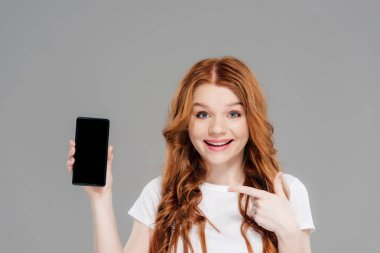 Beautiful redhead girl pointing with finger at smartphone with blank screen, looking at camera and smiling isolated on grey stock vector