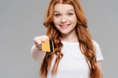 Beautiful smiling redhead girl looking at camera and showing credit card isolated on grey stock vector