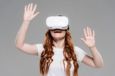 Beautiful redhead girl in vr headset experiencing virtual reality and gesturing with hands isolated on grey stock vector