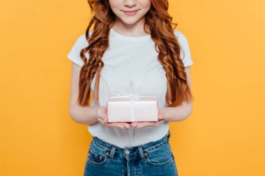 Cropped view of smiling redhead girl holding gift box isolated on yellow stock vector