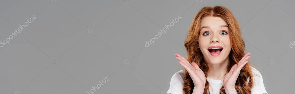 Panoramic shot of beautiful excited redhead girl looking at camera and gesturing with hands isolated on grey