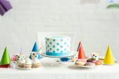lahodné narozeninový dort s koláčky, koblihy a papírových kelímků na sváteční stůl
