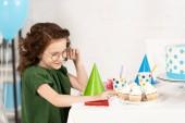 imádnivaló gyerek ül az asztalnál Cupcakes során születésnapi ünnepség