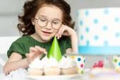 imádnivaló preteen ül az asztalnál, és néztem Cupcakes születésnapi ünnepség során otthon