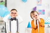 Fotografia adorabile ragazzi preteen guardando la macchina fotografica attraverso le dita durante la festa di compleanno