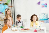 adorable kids sitting at table and waiting for cake during birthday party