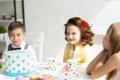 Fotografia bambini adorabili seduti a tavola con la torta durante la festa di compleanno a casa