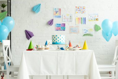 festive cake and party caps on table in room decorated for birthday party with air balloons