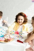 adorable kids sitting at table with donuts during birthday party at home