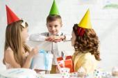 bambini adorabili in tappi di partito seduti al tavolo con scatole regalo durante la festa di compleanno a casa
