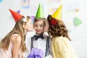 Fotografia bambini in tappi Partito baciare su guance adorabile ragazzo con scatola regalo durante la festa di compleanno a casa