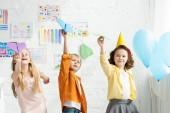 rozkošné děti hrající na papírové letouny během narozeninového večírku doma