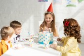 adorable happy kids sitting at party table with cake while celebrating birthday together