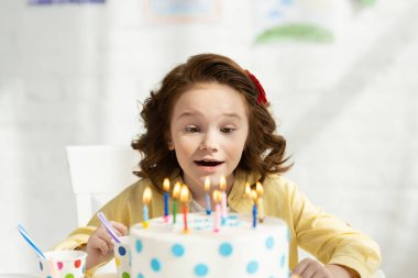 Selective focus of adorable preteen sitting at table with birthday cake at home stock vector