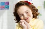 Fotografia adorabile bambino sorridente appoggiato la testa sulle mani a casa