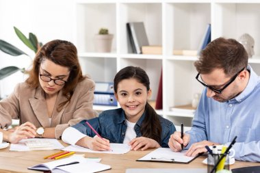 cute child drawing near parents in glasses working in office