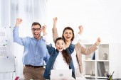 cheerful family celebrating triumph near laptop in office