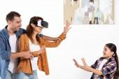 glücklicher Mann hält Hand einer fröhlichen Frau in Virtual-Reality-Headset in der Nähe der Tochter