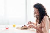 Seitenansicht eines lächelnden Mädchens, das Pfannkuchen in der Küche isst