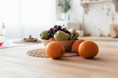 bowl with apples, bananas, grapes and oranges on table