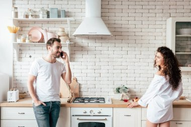 smiling couple looking at each other in morning in kitchen