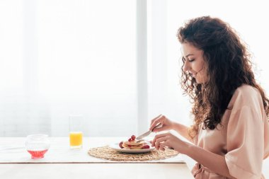 side view of smiling girl eating pancakes in kitchen