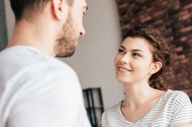 joyful attractive girl looking at boyfriend with smile