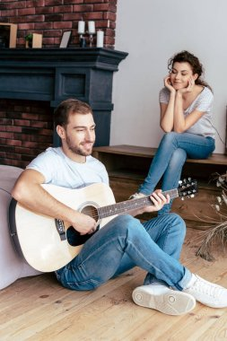smiling bearded man playing acoustic guitar to girlfriend in living room