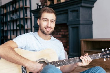 smiling bearded man playing acoustic guitar in living room