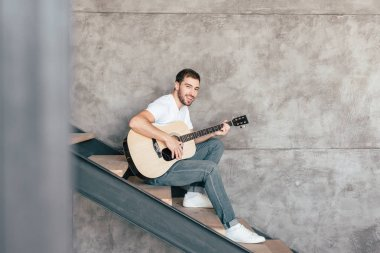smiling bearded man sitting on stairs and playing acoustic guitar