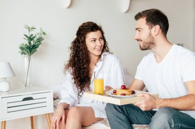 Smiling couple with tray with breakfast looking at each other in bedroom stock vector