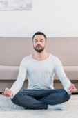 Photo handsome man with eyes closed sitting on carpet in Lotus Pose and meditating at home